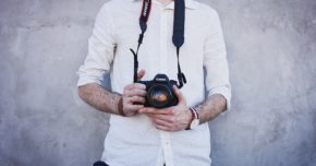 a photographer in a white shirt by a wall